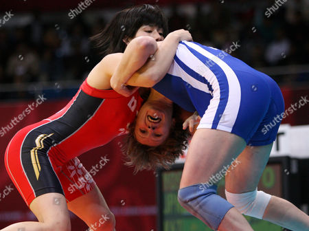 WRESTLING Japan's Saori Yoshida, in red,holds on to Kazakhstan's Olga Smirnova during the Women's Freestyle Wrestling 55kg final for the 15th Asian Games in Doha, Qatar, . Yoshida defeated Smirnova to take gold