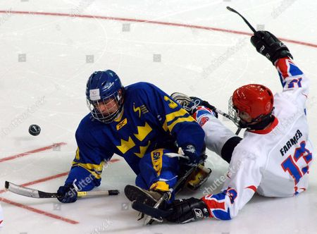 Peter Melander of Sweden, left, is challenged by Gary Farmer of Great Britain, during their ice sledge hockey match, at the Turin 2006 Paralympic Winter Games at the Turin Esposizioni arena in Turin, Italy