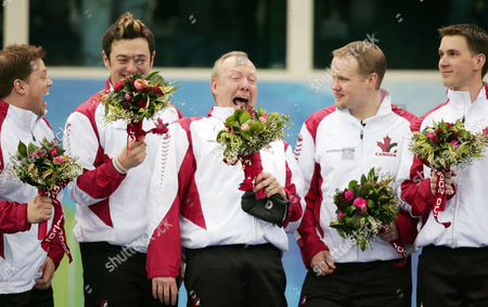 Canadian skip Russ Howard, center, laughs with his team from left, alternate Mike Adam, Jamie Korab, Howard, Mark Nichols and Brad Gushue after they won the gold medal in curling against Finland in Pinerolo, Italy during the Turin 2006 Winter Olympic Games on