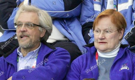 Finland's President Tarja Halonen and husband Dr. Pentti Arajarvi, left, watch Finland play Canada during the gold medal match in curling in Pinerolo, Italy during the Turin 2006 Winter Olympic Games on
