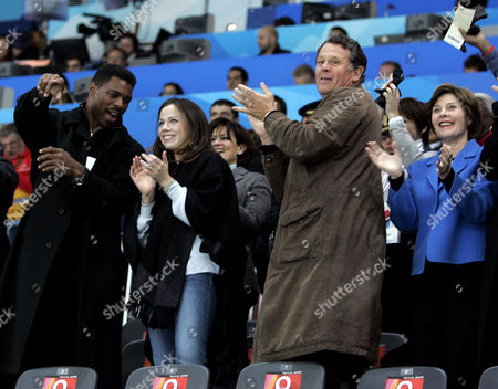 Stock Picture of BUSH U.S. first lady Laura Bush, right, and her delegation, from left to right: former Olympian Herschel Walker, Barbara Bush, and Roland Betts, during the second goal scored by the United States against Switzerland during second half action of Women's Ice Hockey at the 2006 Winter Olympics in Turin, Italy