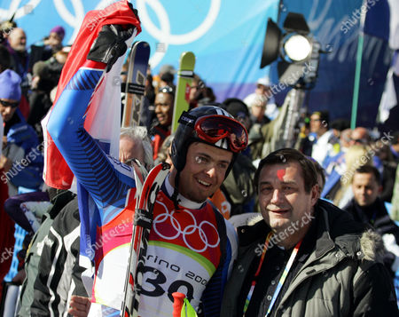 Antoine Deneriaz of France, left, celebrates with French politician Jean Francois Lamour, after clinching the gold medal of the Men's Downhill at the Turin 2006 Winter Olympic Games in Sestriere Borgata, Italy