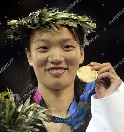 ZHONG Chen Zhong, from China, displays her gold medal after defeating Myriam Baverel, from France, in women's over 67kg taekwondo at the 2004 Olympic Games in Athens, Greece