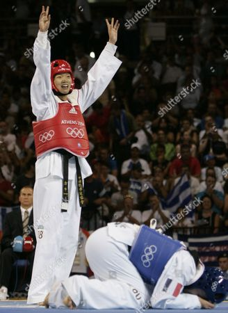 CHEN BAVEREL Chen Zhong, from China, celebrates after defeating Myriam Baverel, on mat, from France, to win the gold medal in women's over 67kg taekwondo at the 2004 Olympic Games in Athens, Greece