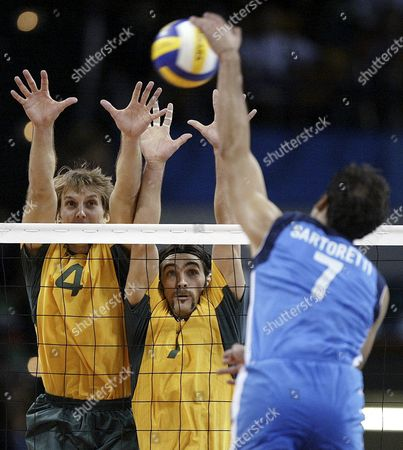 Brazil's Andre Heller (4) and Gilberto Godoy Filho go up to block the spike of Italy's Andrea Sartoretti during their gold medal match at the 2004 Olympics Games in Athens, . Brazil won 25-15, 24-26, 25-20, 25-22