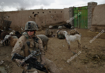 In this image made, U.S. Marine Cpl. Justin Pollard, 22, from Santa Clarida, CA, sits in the courtyard of a mud compound during a patrol with 3rd Platoon, India Company, 3rd Battalion, 5th Marine Regiment in Sangin district southern Helmand province of Afghanistan. U.S. Marines battling the Taliban in this key insurgent stronghold in southern Afghanistan are increasingly dubious about the prospects for a high-profile peace deal struck two months ago between the government and the area's largest tribe