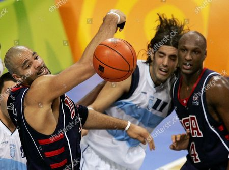 USA's Carlos Boozer, left, can't handle the loose ball as Argentina's Luis Alberto Scola (11) grapples with Lamar Odom, right, during the men's basketball semi-final at the 2004 Olympic Games in Athens