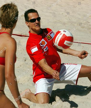 SCHUMACHER COOK Germany's Ferrari Formula One champion Michael Schumacher, right, plays a shot as he is watched by his partner Australia's Olympic gold medalist Natalie Cook during a promotional beach volleyball game at Melbourne's St. Kilda Beach, Australia, . Schumacher will race in this weekend's season opening Grand Prix at Melbourne's Albert park circuit