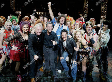 """Stock Picture of YOU The cast of the musical by Queen and Ben Elton """"We Will Rock You"""" including, from left in front row, Kate Hoolihan, who plays Scaramouche, Queen member Roger Taylor, Ben Elton, Brian May, of Queen, with arm raised, and Michael Falzon,leather jacket, who plays Galileo, after a dress rehersal in Sydney, Australia"""