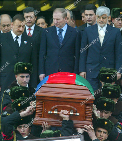 Officers carry the national flag draped coffin, with the body of former Azerbaijan President Geidar Aliev, as Azerbaijan President Ilkham Aliev, top left, Ukranian President Leonid Kuchma, top center, and Iranian First Vice President Muhammed Reza Arif, top right, follow them during a funeral ceremony in Baku, Azerbaijan, . The 80-year-old leader's death Friday at the Cleveland Clinic in Ohio puts the focus now on his son and successor amid questions whether he has the stature to carry on his father's legacy in this former Soviet republic of 8 million