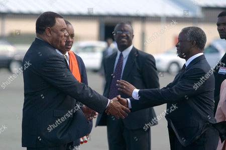 LEFT South African President Thabo Mbeki, right, shakes hands with Bahamian Prime Minister Perry Christie after arriving at Nassau International Airport in Nassau, Bahamas. President Mbeki, accompanied by his wife Madame Zanele Mbeki, arrived in the capital for a four day visit where he will attend a State Reception at Government House and a meeting with Prime Minister Perry Christie and his Cabinet and will have the opportunity to view the Junkanoo street festival before leaving for Haiti on Jan. 1, 2004