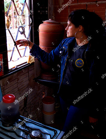 Miriam Alves Pereira handcuffs herself to the window of her home to prevent police from bulldozing it in Taguatinga, 55 km (35 miles) west of Brasilia, Brazil, . Police started the eviciton and destruction of about 150 homes built by poor families of military policemen who work in Brasilia. They had settled in an empty lot owned by the country's capital two weeks ago. The eviction of the policemen's families comes at a time when thousands of families of the Workers Without a Roof Movement still occupy a lot owned by Volkswagen and two vacant apartment buildings in Sao Paulo