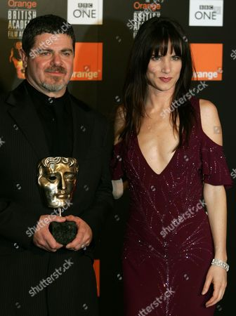 LEWIS Gustavo Santaolalla, left, stands alongside Juliette Lewis as he holds the Anthony Asquith award for Achievement in Film Music at the British Academy Film Awards in London's Leicester Square