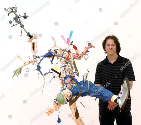 U.S. artist Tom Friedman poses with one of his works of art 'untitled 2004', a sculpture made out of construction paper suspended from the ceiling with monofilament, during a press preveiw of his 'Solo Show' in London, . Friedman's 'Solo Show' runs at the South London gallery from June 15- Aug. 1, 2004