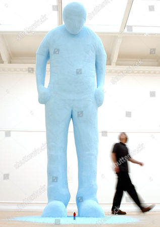 U.S. artist Tom Friedman walks past one of his works of art 'untitled 2004', a giant figure and a tiny figure carved out of styrofoam, during a press preview of his 'Solo Show' in London, . Friedman's 'Solo Show' runs at the South London Gallery from June 15- Aug. 1, 2004