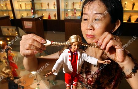 "BARBIE CHOU Former Barbie assembly line worker Chou Su-chin, 50, grooms a Barbie doll at the makeshift Barbie museum, in the northern industrial town of Taishan, Taiwan. When U.S. toy maker Mattel Inc. began outsourcing Barbie-making jobs to Asia, Taishan was among the first places to get a factory in 1967. Although the plant closed 17 years ago as Mattel found cheaper labor in China and Indonesia, the town is trying to keep Barbie's legacy alive with a new museum _ which is actually more like a shrine _ devoted to the doll. Chou explained that to be a ""Mattel Girl"" was a very special title and was an envy of all young girls in the area"
