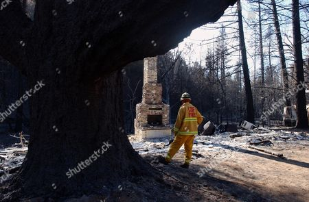 LAWSON Jeremy Lawson of the Sonoma Lake/Napa CDF, looks at a burned down home near The Geysers, Calif., . An infusion of fresh firefighters allowed officials to get the upper hand Tuesday on a wildfire that has burned more than 12,500 acres of land in Northern California's wine country