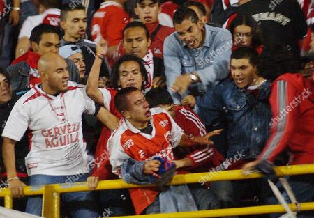 Jason Ruiz, a fan of the Santa Fe soccer team, is beaten during riots that erupted after America de Cali defeated Santa Fe 5-2 in a Colombian first division game in Bogota, . Ruiz was later taken to the hospital suffering severe head injuries