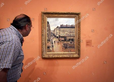 "An unidentified visitor looks at the Impressionist painting called ""Rue St.-Honore, Apres-Midi, Effet de Pluie"" painted in 1897 by Camille Pissarro, on display in the Thyssen-Bornemisza Museum in Madrid. A federal judge in California has dealt a blow to a Jewish family's prolonged battle to regain ownership of the masterpiece seized from a woman fleeing Nazi Germany in 1939 and now on display in the museum in Spain. Judge John Walter found that under Spanish law, the Thyssen-Bornemisza Museum in Madrid is the rightful owner of ""Rue Saint-Honore, Apres-midi, Effet de Pluie."" In last week's ruling, Walter dismissed a 2005 lawsuit filed by the woman's heirs against the museum, but urged the institution to consider what would be fair to victims of Nazi persecution"