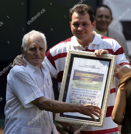 Cuban pitcher Conrado Marrero, left, former player of the Senators of Washington receives an award from Cuban President of the Sport Institute Humberto Rodriguez during the opening ceremony of the 35th baseball world championships, Sunday Oct.12, 2003 in Havana, Cuba