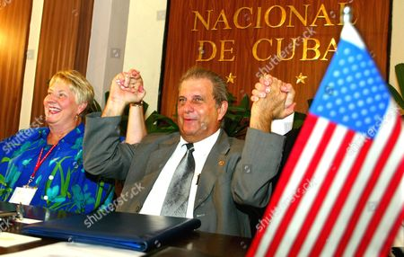 CUBA US IOWA Sen. Nancy Boettger, R-Harlan, left, from Iowa and Cuban Pedro Alvarez, president of the state company Alimport celebrate hold hands after signing agreements between Cuba and Iowa, in Havana, Cuba