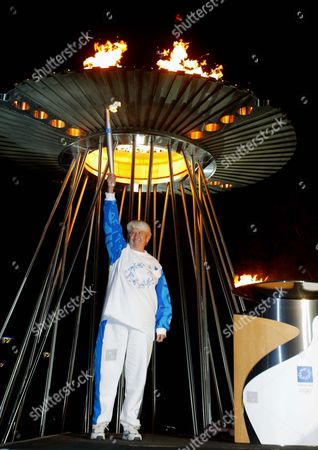 FRASER Australian Olympian Dawn Fraser holds a relay torch high in the air after lighting it from the caldron at Homebush in Sydney, home of the 2000 Sydney Olympics, Australia, during the Athens 2004 Olympic Torch Relay