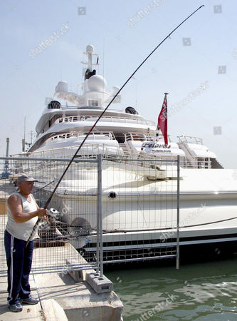 "PELORUS A man fishes next to the ""Pelurus"", the luxury yacht owned by the Russian billionaire Roman Abramovic, in the harbour of Lisbon, Portugal, on . Abramovic, president of the English Premier League soccer team Chelsea, is expected to watch some Euro 2004 soccer matches in Portugal"