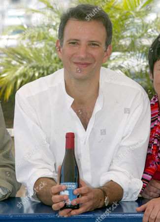 """NOSSITER American film director Jonathan Nossiter displays a bottle of wine with the label for his film during a photocall for his film """"Mondovino"""" shown in competition at the 57th International film festival in Cannes, southern France, . """"Modovino"""" is a documentary about wine across three continents"""