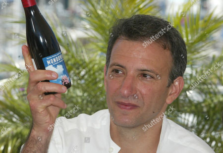 """NOSSITER American film director Jonathan Nossiter holds up a bottle of wine with the label for his film during a photocall for his film """"Mondovino,"""" which is being shown in competition at the 57th International film festival in Cannes, southern France, . """"Modovino"""" is a documentary about wine across three continents"""