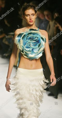 A model presents a peony-like flower as a halter top with a feathery flapper-like full-length skirt by Japanese fashion designer Naoki Takizawa for Issey Miyake's spring-summer 2005 ready-to-wear fashion collection, presented, in Paris