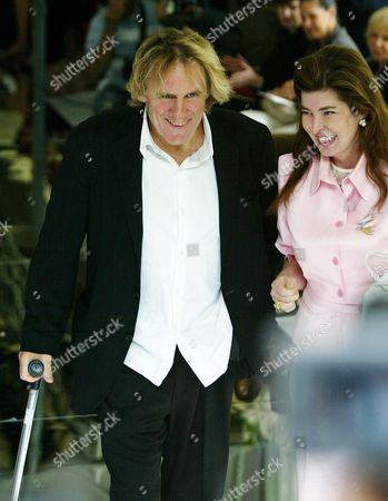 Stock Picture of DEPARDIEU French actor Gerard Depardieu, using a cane, arrives to attend Jean-Louis Scherrer's fall-winter 2004-2005 fashion collection showing, in Paris, . Depardieu suffered minor injuries following a recent scooter accident in Paris. At right is Sophie Dumenil, wife of Alain Dumenil, owner of Scherrer trademark