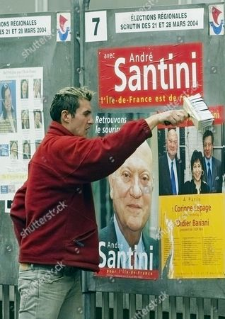 A militant sticks up an electoral poster for centrist candidate Andre Santini in Paris, ahead of Sunday's regional elections. The oppostion accused France's conservative government of using fears of terrorism to get votes in regional elections, just as Prime Minister Jean-Piere Raffarin said the best way to fight terror is to vote