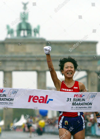 Japan's Yoko Shibui celebrates as she crosses the finish line to win the women's competition at the Berlin Marathon on . Around 36,000 athletes took part in the Berlin Marathon. In the background is the Brandenburg Gate