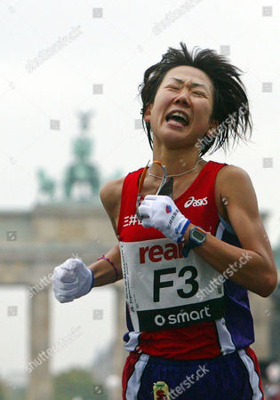 Japan's Yoko Shibui grimaces as she crosses the finish line to win the women's competition at the Berlin Marathon on . Around 36,000 athletes took part in the Berlin Marathon. In the background is the Brandenburg Gate