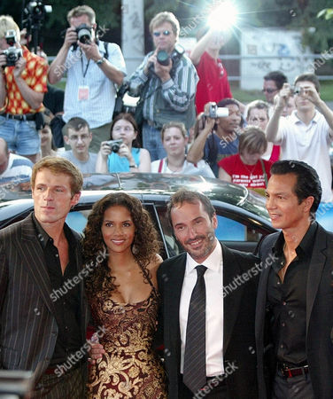 """Stock Image of NOVI Lambert Wilson, left, Halle Berry, director Pitof, and Benjamin Bratt,right, pose for photographers after their arrival for the German premiere of their new movie """"Catwoman"""" in Hamburg, northern Germany, on"""