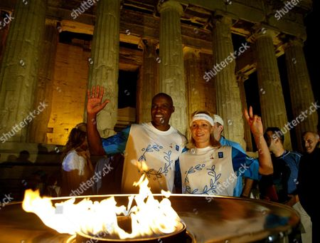 Stock Picture of Nine times olympic gold medal winner Carl Lewis of the United States, left, and Greek Olympic medalist Niki Bakoyianni, right, pose for the photographers in front of the Olympic flame in front of the columns of the ancient Parthenon temple at the Acropolis hill . The Olympic flame will stay overnight at the Parthenon on the eve of the opening ceremony of the Athens 2004 Olympic Games