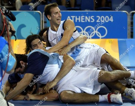 GINOBILI The Argentine team piles onto Emanuel David Ginobili, bottom, after Ginobili hit a last second shot to defeat Serbia and Montenegro in a preliminary round game at the Helliniko Indoor Arena in Helliniko, Greece during the 2004 Olympics Games, . Argentina defeated Serbia and Montenegro 83-82