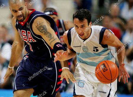 BOOZER GINOBILI The USA's Carlos Boozer (7) reaches in to try and steal the ball from Argentina's Emanuel Ginobili in the first period of their game at the Olympic Indoor Hall during the 2004 Olympics in Athens, Greece on