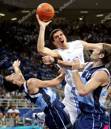 GINOBILI OBERTO TSARTSARIS Greece's Konstantinos Tsartsaris commits an offensive foul as he tries to shoot over Argentina's Emanuel David Ginobili, left, and Fabricio Oberto, right, in the fourth quarter of their game at the Olympic Indoor Hall during the 2004 Olympics in Athens, Greece on . Argentina beat Greece 69-64