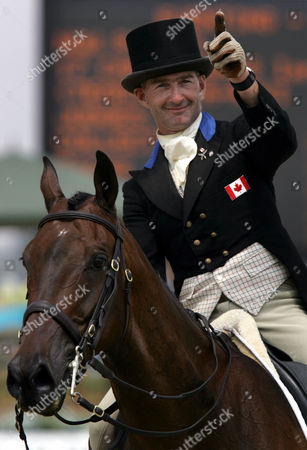 ROBERTS Canada's Ian Roberts waves to the crowd as he rides Mata-Riki as they leave the dressage arena after completing the first portion of the three-day event competition at the Markopoulo Olympic Equestrian Center near Athens