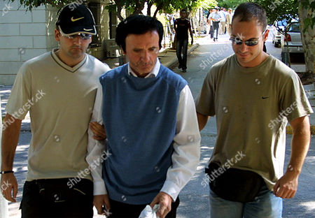 Defrocked Irish priest Cornelius Horan, 57, center, is escorted by plain-clothed police officers at a court in Athens on . The three member court found Horan guilty of violating Greek laws on disrupting sports events outside of a stadium after he attacked Brazilian marathoner Vanderlei de Lima on Sunday, knocking him into the crowd. Lima, who was ahead of the field with about three miles at the time of the attack, continued running but lost his lead and finished third