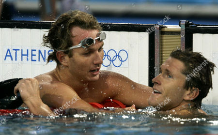 Aaron Peirsol, of the United States, left, celebrates with Lenny Krayzelburg after Peirsol won the gold medal in the 100-meter backstroke at the Olympic Aquatic Centre during the 2004 Olympic Games in Athens