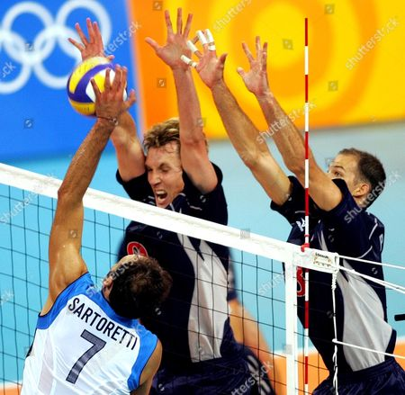 PRIDDY MILLAR Italy's Andrea Sartoretti spikes the ball as the USA's Ryan Millar, center, and William Priddy try to block it during their preliminary round match at the 2004 Olympic Games in Athens . Italy won 25-21, 21-25, 25-17, 25-23