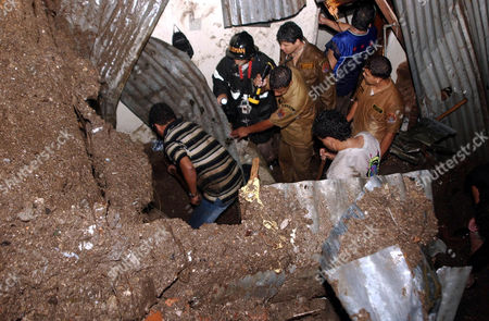 Stock Image of MEDINA Firemen dig through rubble to recover the body of Maria Cristina Medina, 40, who died, after her house collapsed after heavy rainfall in the Los Altos de la Divanna neighborhood of Tegucigalpa, Honduras