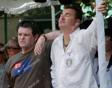 """CSABI HUGHES Bali bombing survivors Peter Hughes, left, of Perth, Australia, and Andrew Csabi, of Gold Coast, Australia, listen as the Australian folk song """"Waltzing Matilda"""" is played outside the Bali bombing memorial site during a wreath laying ceremony for the families of the victims, in Bali, Indonesia. Relatives of the 202 people killed when terrorist bombs ripped through nightclubs on Indonesia's Bali island two years ago gathered at the attack site Tuesday to remember the dead"""