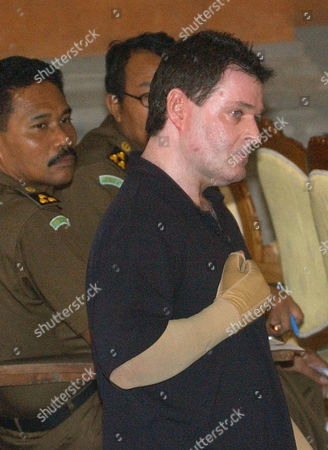 HUGHES Witness and victim of last year's Oct. 12 Bali bombing Peter Hughes, 43, touches his hand to his chest as he approaches the stand to testify against Amrozi bin Nurhasyim in Denpasar, Bali, Indonesia, . Amrozi is on trial for the nightclub blasts that killed 202 people, mostly foreign tourists