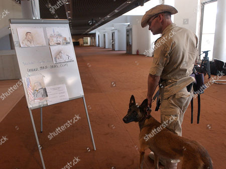 A private security guard with his dog looks at artist's sketches of the U.S. Army Spc. Armin J. Cruz where the court martial take place in Baghdad, Iraq, . The first U.S. military intelligence soldier to be court martialed over the Abu Ghraib abuse scandal, was sentenced to eight months in jail, a reduction in rank and a bad conduct discharge, by the military judge, Col. James Pohl, on Saturday