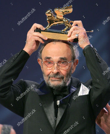 U.S. movie director Stanley Donen holds up the Golden Lion award he won for lifetime achievement at the 61st edition of the Venice Film Festival in Venice, northern Italy