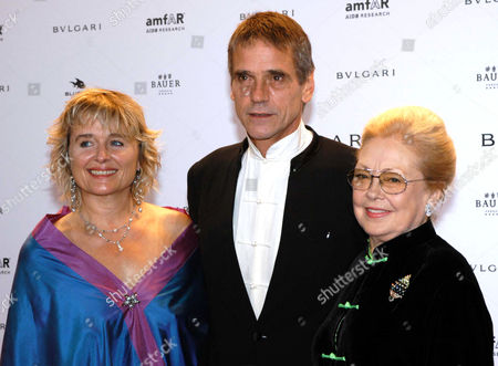 """British actor Jeremy Irons, center, poses with his wife Sinead Cusack, left, and AMFAR, American Foundation for AIDS Research, president Mathilde Krim as they arrive at the """"Cinema Against AIDS Venice 2004"""" event in the island of San Giorgio Maggiore in the Venice lagoon"""