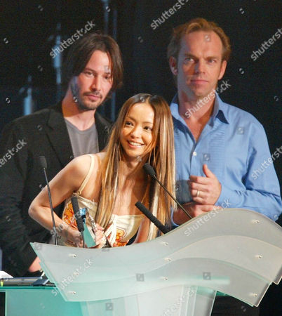 """AMURO REEVES WEAVING Japanese pop singer Namie Amuro smiles after receiving the """"Best Collaboration"""" award as presenters Keanu Reeves, left in background, and Hugo Weaving look on during the MTV Video Music Awards Japan 2003 in Saitama, near Tokyo"""